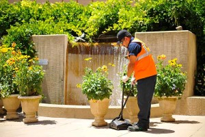 A day porter in reno sweeps up in front of a fountain