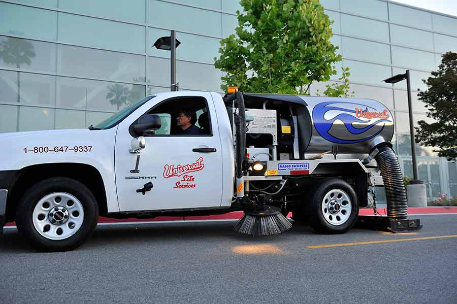 Parking lot sweeping service by Universal Site Services in angled parking lot.