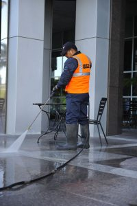 San Diego day porter using a pressure washer to clean a business parking lot