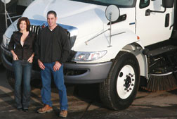 Gina Vella and Joe Vella In Front Of Sweeping Truck